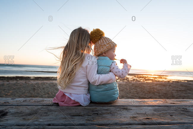 Two sisters sitting together on a picnic table on a beach at sunset