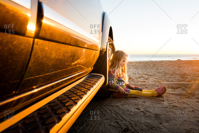 Little girl sitting against a car tire on a beach at sunset
