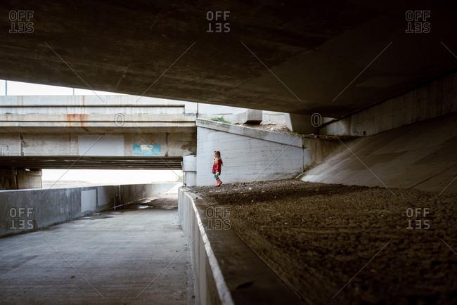 Little girl standing beneath concrete overpasses