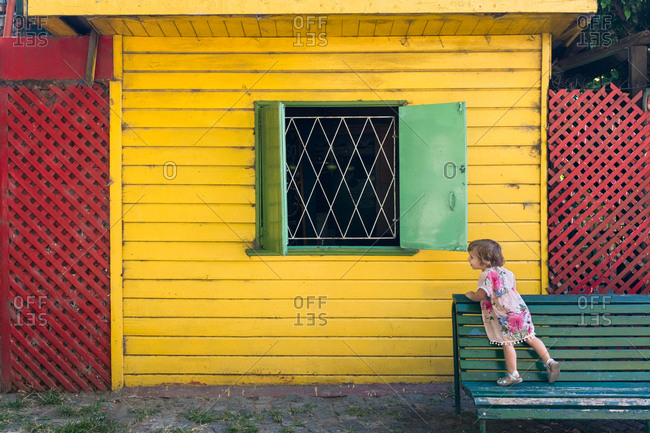 Young girl looking into the window of a yellow house