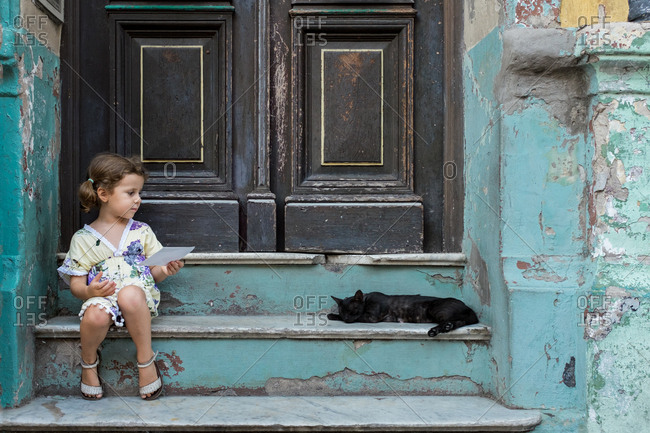 Girl sitting on steps looking at a black cat