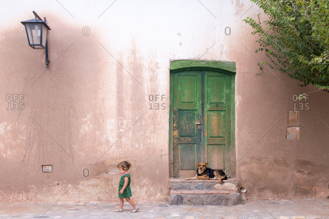 Young girl walking past a dog in the street, in a small Argentinian town