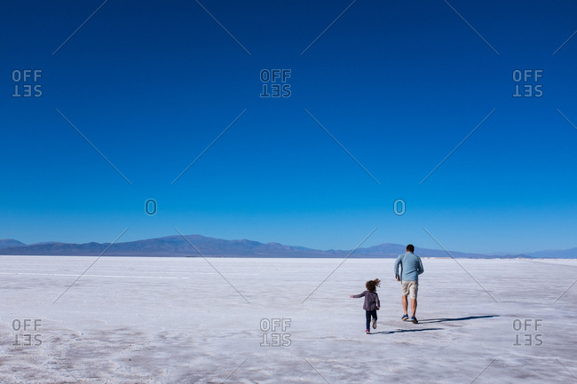 Father and daughter running through salt flats