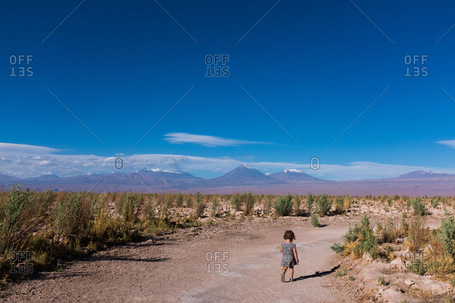 Young girl walking along a path through the desert with mountains in the distance