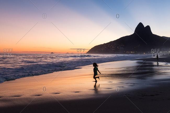 Girl running through the water on Ipanema beach at sunset, Rio de Janeiro