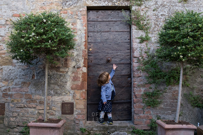 Young girl reaching for the door in a small town in Tuscany