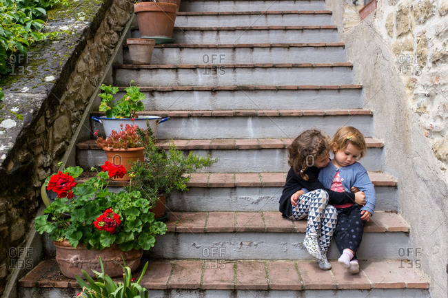 Tow sisters sitting together on the stairs
