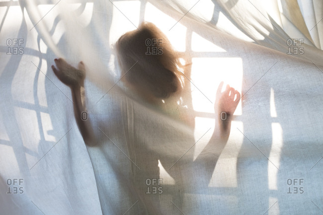 Silhouette of a young girl behind a curtain