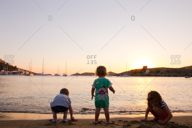 Children playing on the beach as the sun goes down