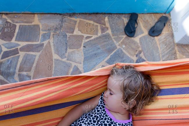 Toddler asleep on a hammock outdoors