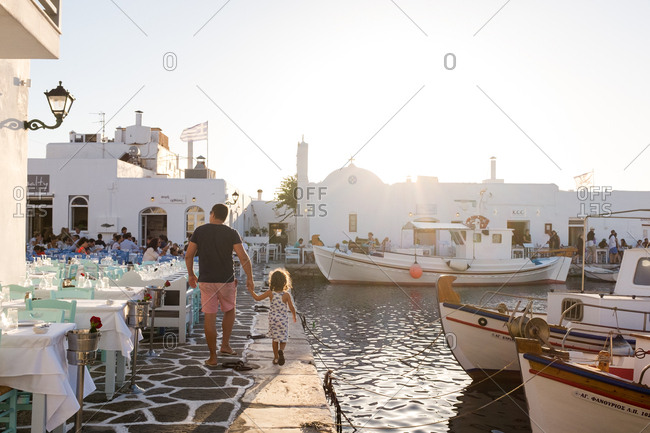 Father and daughter walking along the port on the island of Paros, Greece