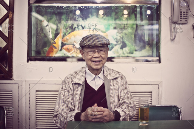 Hong Kong, China - February 5, 2011: A well dressed Chinese gentleman is enjoying his glass of water at a restaurant in Hong Kong.