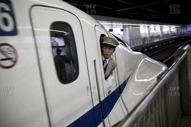 Tokyo, Japan - July 13, 2011: A train conductor is looking out the window from the a high-speed Shinkansen train.
