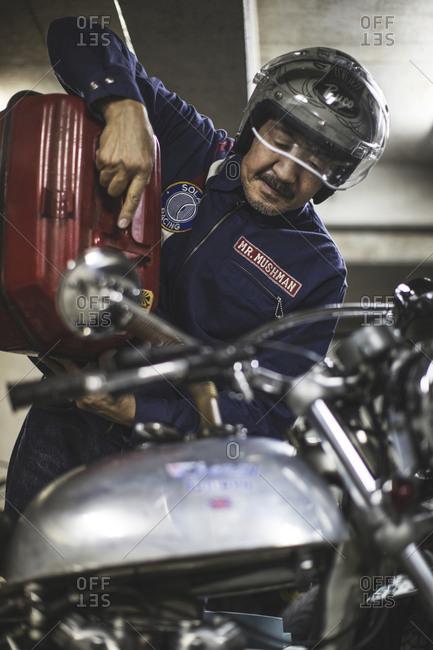 Tokyo, Japan - May 18, 2016: Japanese man filling his motorcycle with petrol fuel.