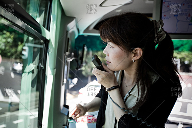 Tokyo, Japan - July 10, 2011: A Japanese tour guide is guiding tourists on a bus trip in Tokyo.