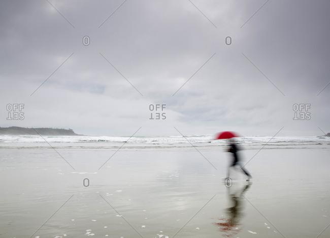 Person on beach with umbrella, British Columbia