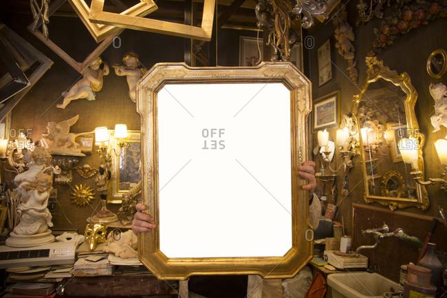 Venice, Italy - April 2, 2013: Frame maker holding golden frame