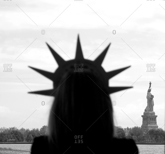 Woman in tourist crown by Statue of Liberty