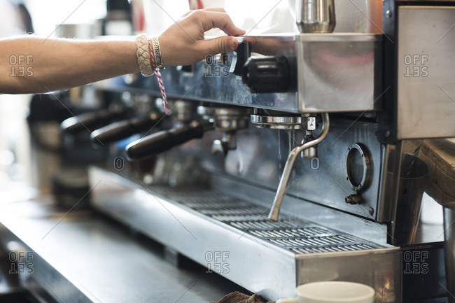 Hand using an espresso machine