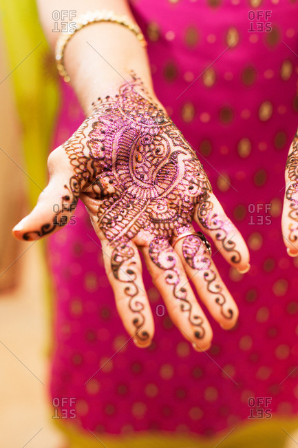 Woman showing freshly applied henna design on her hand at Indian wedding