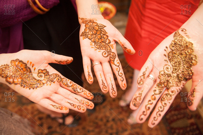 Three women showing freshly applied henna designs on their hands at Indian wedding