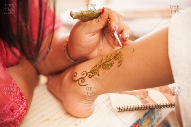 Person applying henna tattoo to leg at Indian wedding