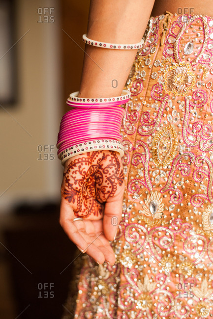 Woman with henna design on hand wearing bangles