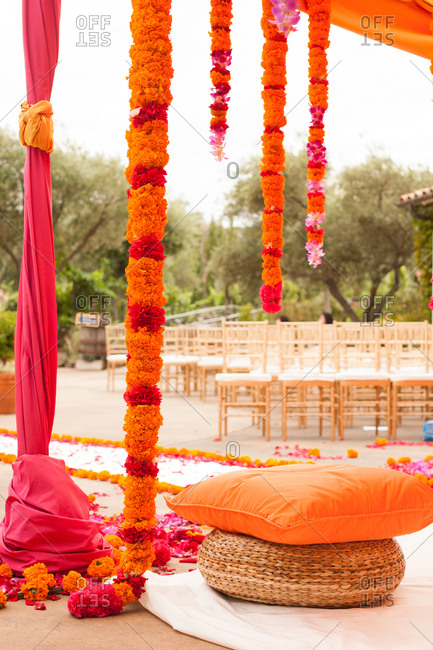 Orange carnations handing from mandap at a traditional Indian wedding