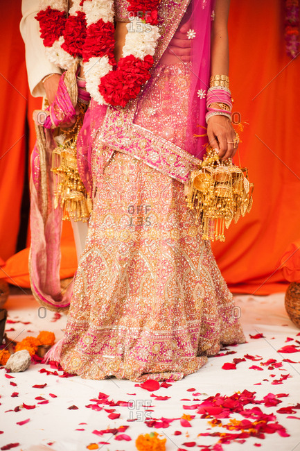Bride wearing lengha and bangles standing under mandap at a traditional Indian wedding