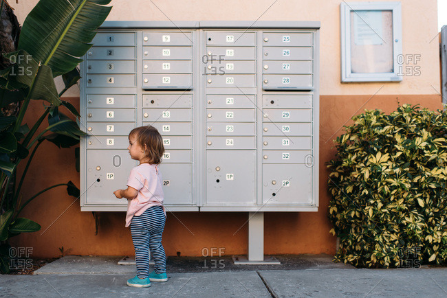 Toddler girl trying to open a mailbox with keys.