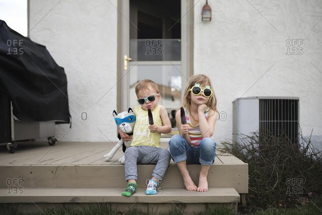 Little kids outside eating popsicles