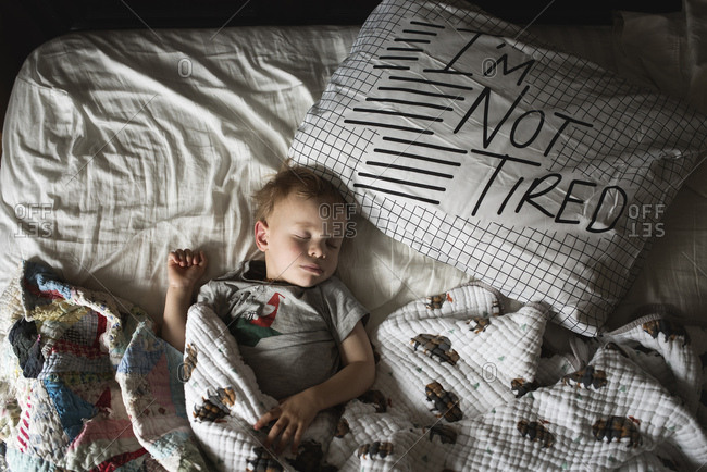"""Boy asleep in bed with pillow that reads """"I'm not tired"""""""
