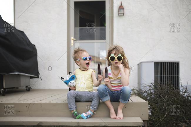 Siblings outside eating popsicles