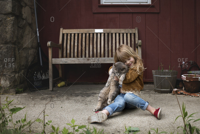 Little girl hugging a kitten outdoors