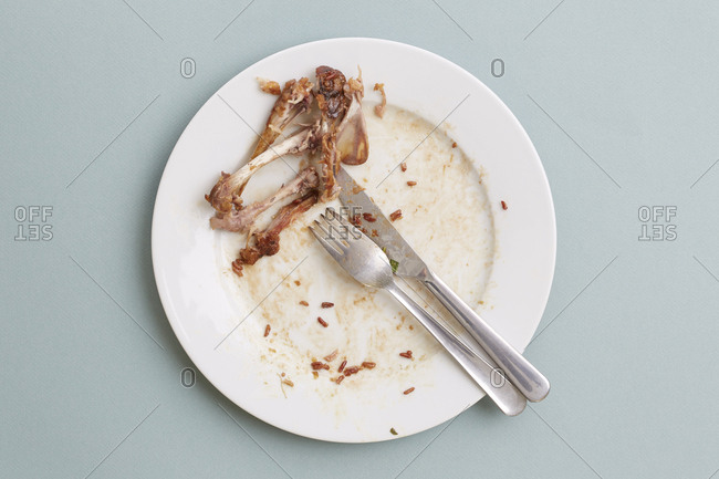 Plate with chicken bones, fork and knife after a meal on blue background