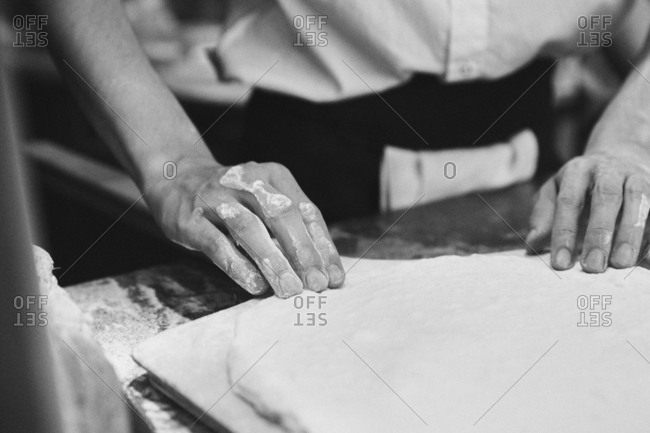 Close-up of hands of Chef making pizza