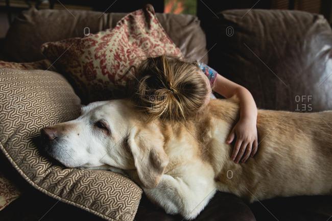 Girl hugging her dog on sofa