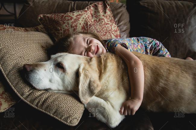 Happy little girl hugging pet dog