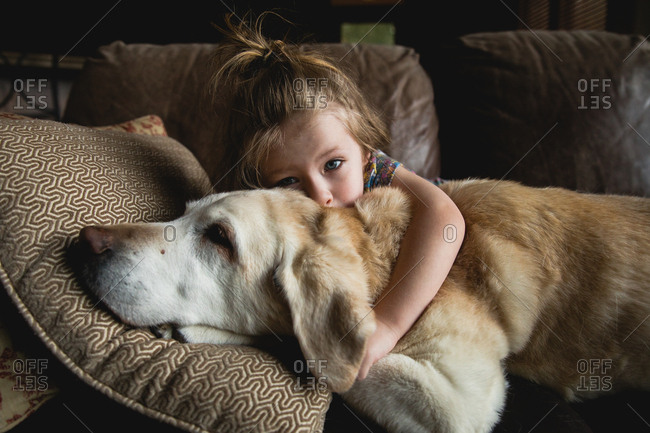 Young girl with arm around her dog