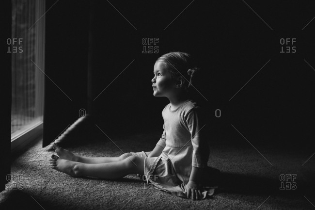 Young girl sitting on carpet in front of sliding door