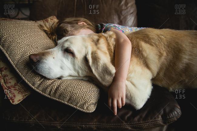 Sleeping girl with arm around her dog