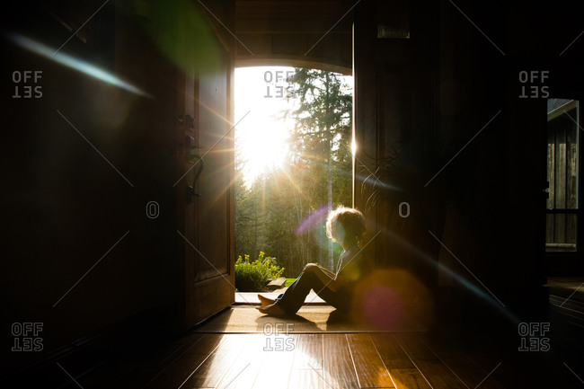 Child sitting in sunlight at open front door