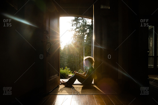 Boy sitting in doorway with sunlight shining in