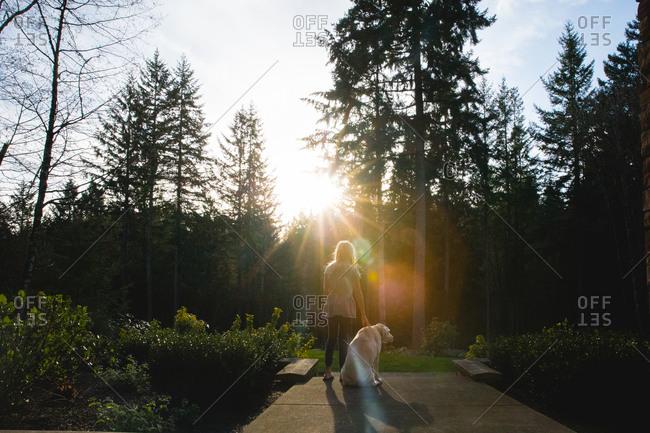 Girl with pet dog in garden