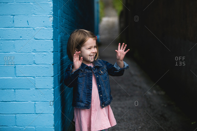 Portrait of happy young girl with both hands raised