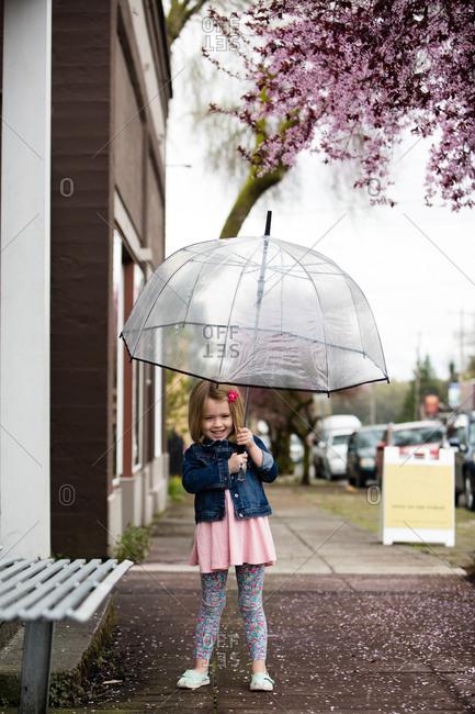 Young girl with umbrella on sidewalk