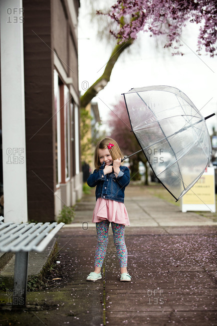Young girl playing with umbrella on sidewalk