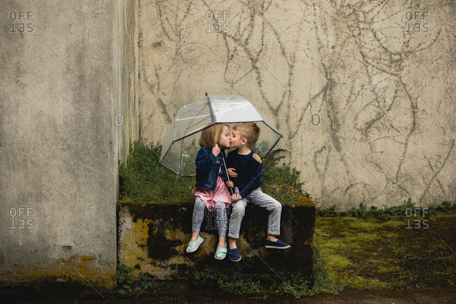 Boy and girl kiss each other under umbrella