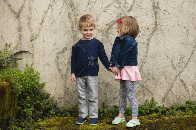 Girl and boy holding hands by wall