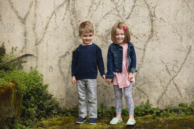 Boy and girl holding hands next to garden wall